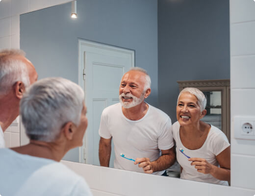 Man and woman brushing their teeth at home