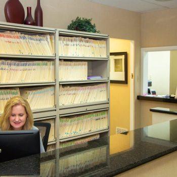 The receptionist for Dr. John Skowron Jr. working at the front desk